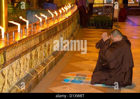 Buddhist monk praying at the Shwedagon Paya located in (Rangoon)Yangon, (Burma) Myanmar. - Stock Photo