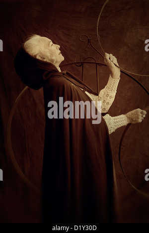 Mature woman wearing a hooded cape holding hoops. - Stock Photo