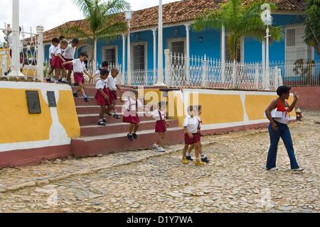 Uniformed schoolchildren marching along street - Stock Photo