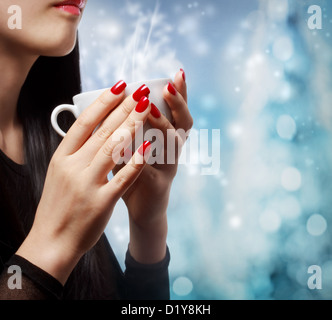 Beautiful woman holding a hot beverage on blue bokeh background - Stock Photo