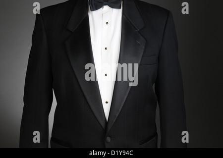 Closeup of a Black Tuxedo Jacket. Torso only on a light to dark gray background. Horizontal format. - Stock Photo