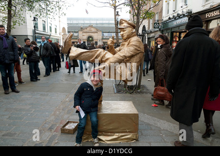 A young boy posing with a street performer in Covent Garden, London UK KATHY DEWITT - Stock Photo