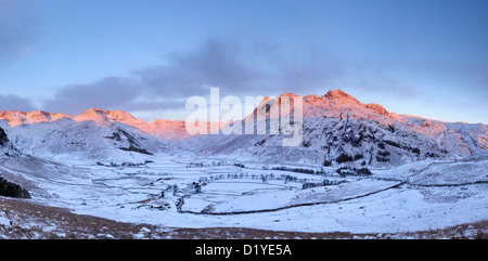 Pink dawn sunlight on the Langdale Pikes and Bowfell in winter in the English Lake District