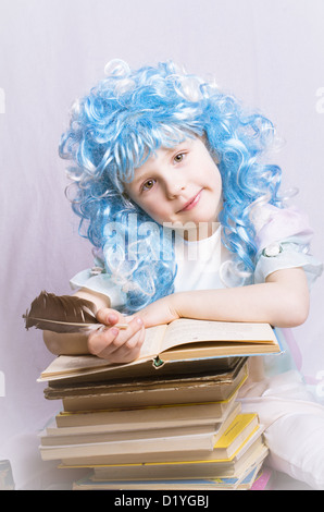 little girl with blue hair and quill pen sitting near stack of books - Stock Photo