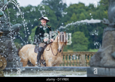 Frederiksborger with rider in historic costume standing behind a fountain in the garden of Frederiksborg Palace - Stock Photo