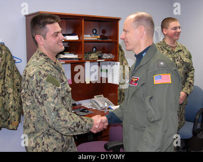 Rear Adm. John Haley, Commander, Carrier Strike Group 5, greets Gunner's Mate 1st Class Michael Stefanelli, a native - Stock Photo