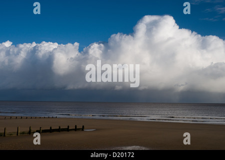 The sun shines on the sandy beach at Frinton-on-sea Essex while heavy rain clouds are a few miles out to sea - Stock Photo