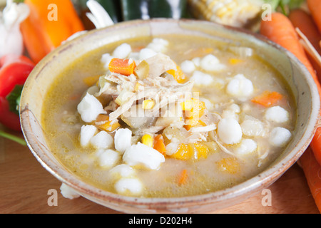 A single serving of a traditional Southwestern stew of chicken posole garnished with fresh vegetables. - Stock Photo