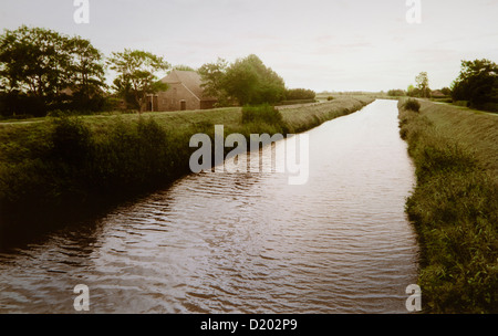 Farm house at a canal, East Frisian Wadden Sea, East Friesland, North Sea, Lower Saxony, Germany, Europe - Stock Photo