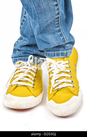 A young woman posing in jeans and yellow sneakers. - Stock Photo