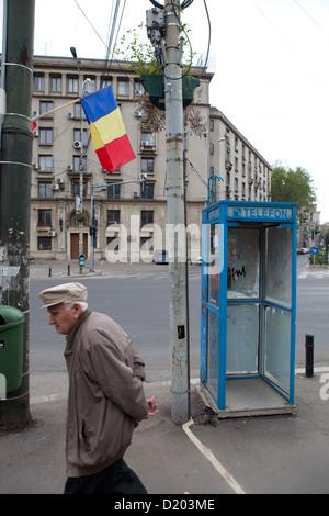 Bucharest, Romania, an old man walks past the romanian flag and Telefonhaeuschen - Stock Photo