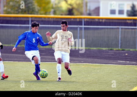 Soccer players compete in the corner deep at the end of the pitch during a high school match. USA. - Stock Photo