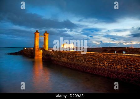Illuminated bridge, Puente de las Bolas and Castillo de San Gabriel in the evening, Arrecife, Lanzarote, Canary - Stock Photo
