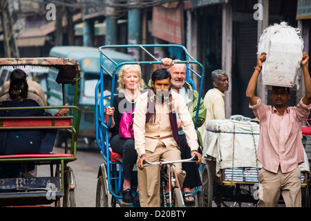 Tourists on a bicyce rickshaw in Old Delhi, India - Stock Photo