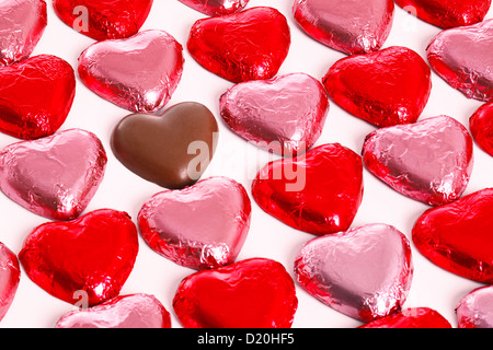 Chocolate hearts in red and pick foil wrappers on a white background, with one unwrapped heart in amongst the group. - Stock Photo