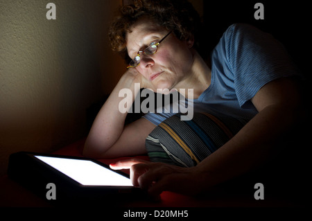 Woman reading a book on an e-reader while in bed - Stock Photo
