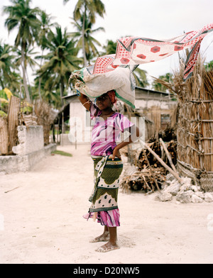 Young woman in traditional cloth Kanga is carrying seaweed, Jambiani, Zanzibar, Tanzania, East Africa - Stock Photo