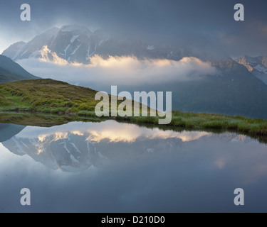 Mountain reflection in a mountain lake, View from Oberberg towards Hochfeiler (3510m), Pfitsch Valley, South Tirol, - Stock Photo