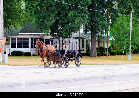USA , Indiana, Middlebury, Elkhart County. Amish buggy full of family members is driven down the main street - Stock Photo