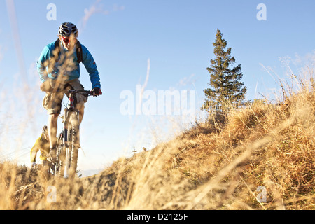 Two mountainbikers riding on a trail in the Alps, Alpspitz, Bavaria, Germany, Europe - Stock Photo