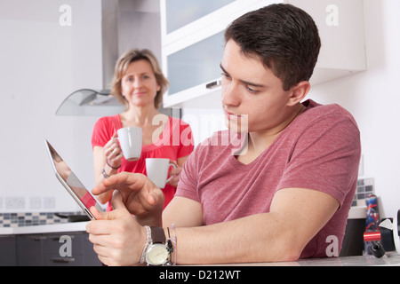 Young man using a digital tablet looking at the screen or monitor. Situated in a modern kitchen a woman holding - Stock Photo