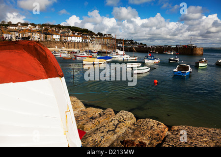 Mousehole harbor harbour Cornwall small fishing boats moored with village in background - Stock Photo
