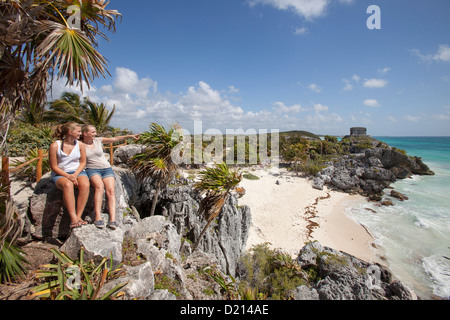 Two young girls and an iguana relaxing on a rock overlooking the beach, ancient Mayan buildings at the Tulum Ruins - Stock Photo
