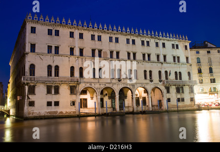 Illuminated Fondaco dei Tedeschi at twilight, Venice, Italy - Stock Photo