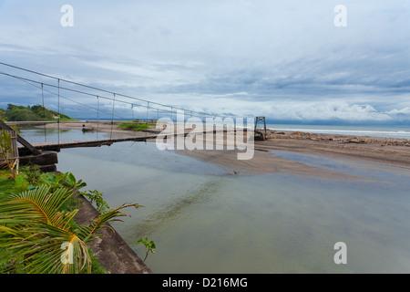 Suspension bridge over small river leading to the sea in Bali. - Stock Photo