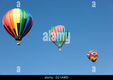 Three colorful hot air balloons floating into a blue sky - Stock Photo