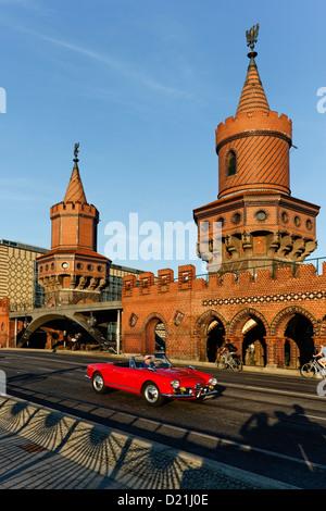 Red cabrio at the Oberbaum Bridge, Oberbaumbruecke over river Spree, architect Otto Stah, Kreuzberg, Berlin - Stock Photo