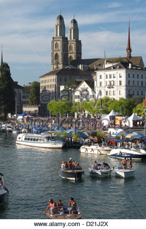 Boats at the Limmat River with the Great Minster in the background, Zurich, Switzerland - Stock Photo