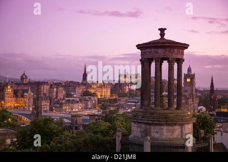 Dugald Stewart Monument on Calton Hill with Edinburgh Castle and cityscape at dusk, Edinburgh, Scotland, United - Stock Photo