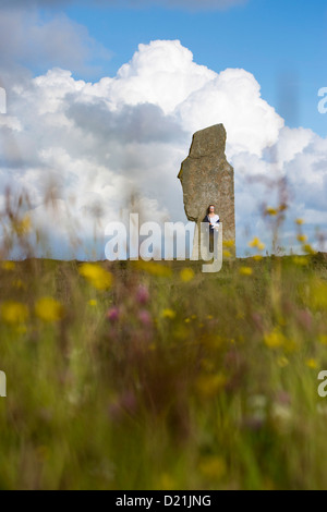 Young woman stands by stone at The Ring of Brodgar circle of Neolithic standing stones, Orkney Islands, Scotland, - Stock Photo
