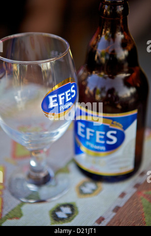Efes Pilsen Beer Bottle and Glass on restaurant Table in Side, Turkey - Stock Photo