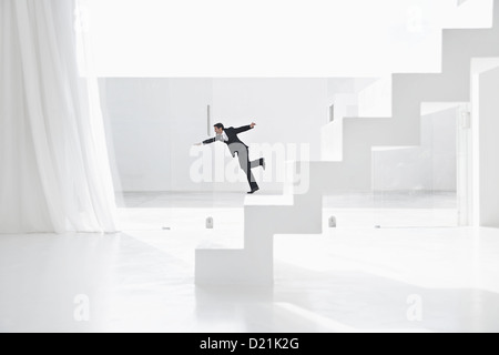Spain, Businessman falling down from ladders - Stock Photo