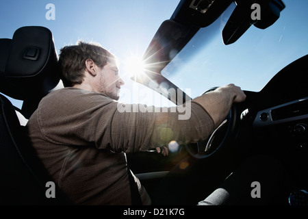 Germany, Bavaria, Mid adult man in car - Stock Photo