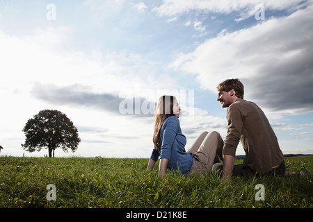 Germany, Bavaria, Couple sitting in field - Stock Photo