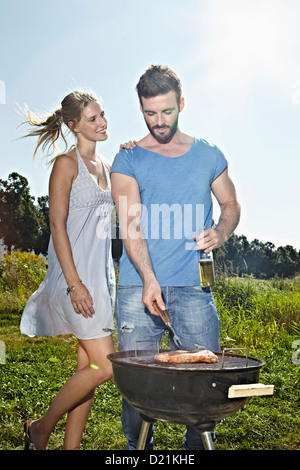 Germany, Cologne, Young couple grilling sausage and drinking beer - Stock Photo