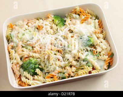 Pasta and broccoli bake, with fusilini tricolori , bechamel sauce and grated parmesan all in a ceramic baking dish - Stock Photo