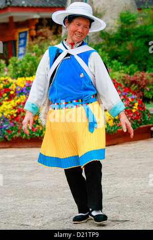 A traditional Naxi woman dancing in the streets of the old town in Lijiang, Yunnan, South West China. - Stock Photo