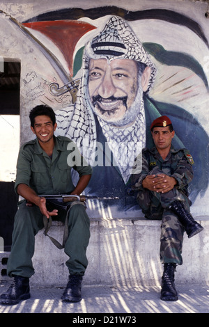Members of the Palestinian National Security Forces sitting in front of a painted figure of Yasser Arafat who was - Stock Photo