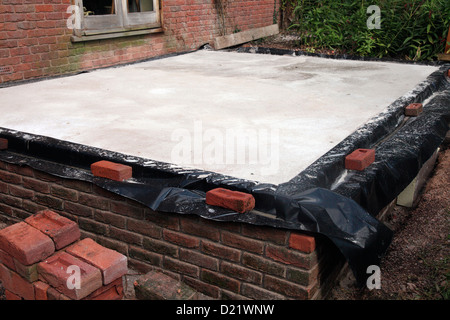 Building a conservatory - dwarf walls up to damp proof course level and concrete pad in place - Stock Photo