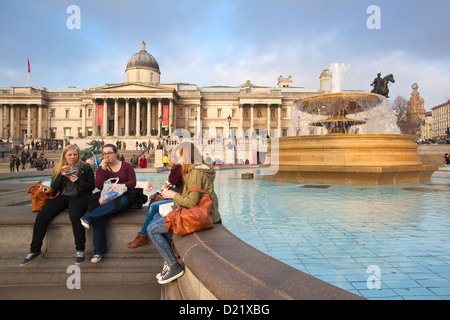 Tourists sitting on the edge of the fountains at Trafalgar Square, with The National Gallery in the background London - Stock Photo