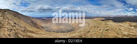 Panorama of the Caldera Blanca volcano. Canary Islands, Lanzarote, Timanfaya National Park. Atlantic Ocean in background. - Stock Photo