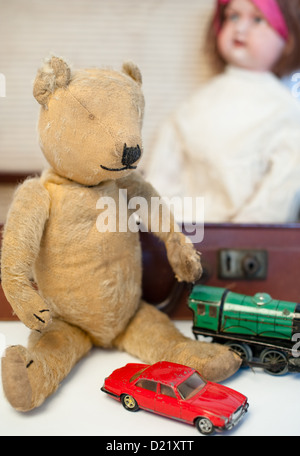 Old-fashioned well-loved vintage teddy bear, a red boys battered dinky car, green train engine and a Victorian china - Stock Photo