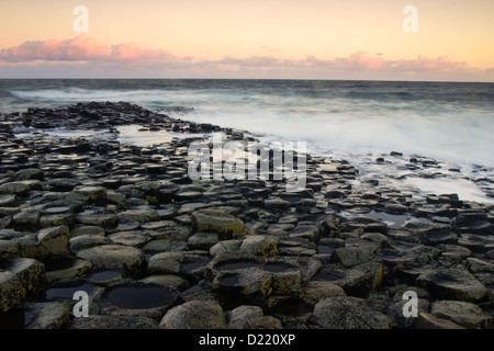 Morning light and strong waves on the Giant's Causeway - landmark of Northern Ireland - Stock Photo