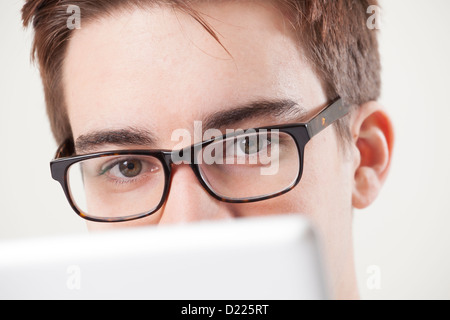 Young male wearing glasses looking to camera, using a laptop or digital tablet. Close up on eyes. - Stock Photo