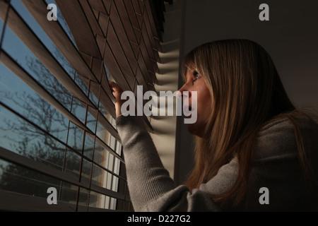 Anxious mature woman peering through window blinds at night.