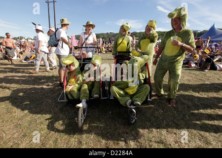 KIDS AND ADULTS DRESSED IN ALIGATOR SUITS IN BUGGIES AT BESTIVAL FESTIVAL, ISLE OF WHITE, SEPTEMBER 2012 - Stock Photo